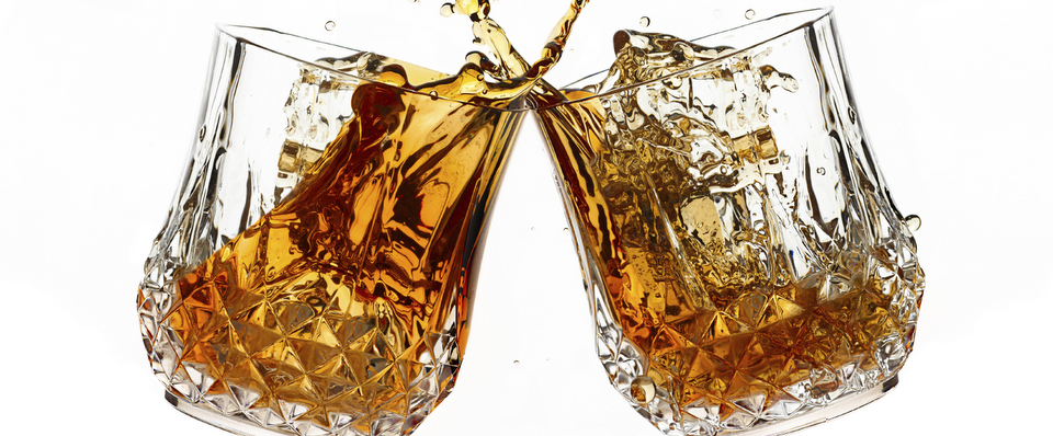 Cheers. A Toast with whiskey. Two glasses clicking together over white background. Splashing whisky on glasses of cut glass